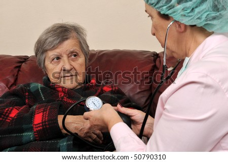 A nurse measuring senior patient's blood pressure â?? series of MEDICAL IMAGES. - stock photo