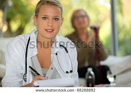 A nurse visiting an elderly patient at home - stock photo