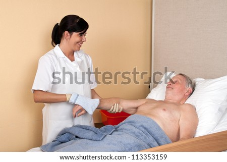a nurse washes a patient - stock photo