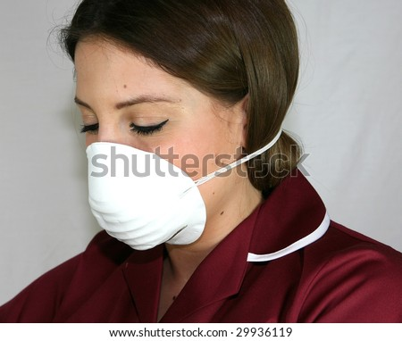 A Nurse wears a face mask to protect against infection - stock photo