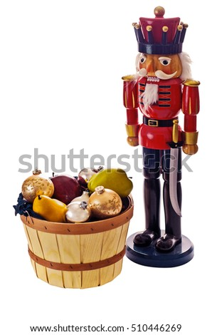 A nutcracker stands over a fruit basket