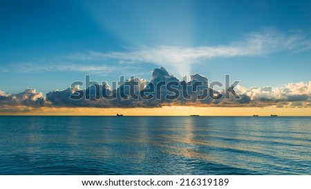 A ocean water surface under cloudy sky. Great impression of distance and solitude. Rays of the rising sun. - stock photo