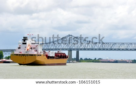 A Oil Tanker Freighter Ship Approaches The Greater New Orleans Mississippi River Bridge - stock photo