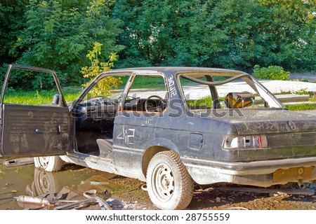 A old abandoned car to background - stock photo