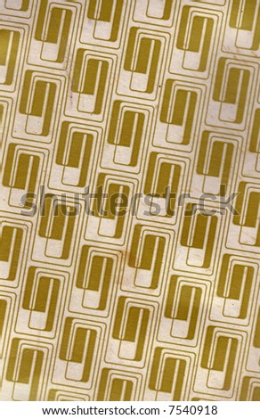 A old grungy cardboard sheet with a gold retro pattern, for uses as a background texture. - stock photo