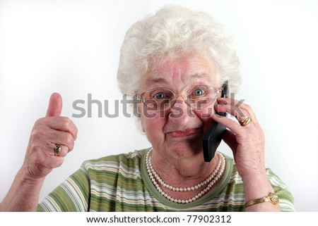 A old lady using a mobile phone - stock photo