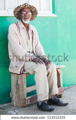 A old man is sitting on a bench outside of his home. - stock photo