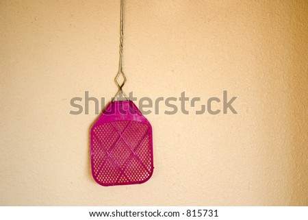 A old purple fly swatter is hanging on a wall - stock photo