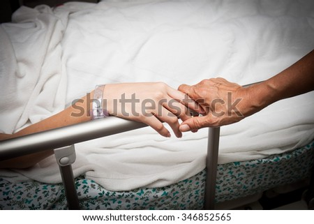 A old wrinkled hand touches and holds young hand - stock photo
