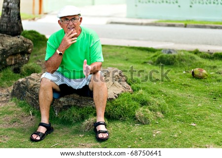 A older Hispanic senior citizen man sits outdoors looking contemplative in a tropical setting. - stock photo