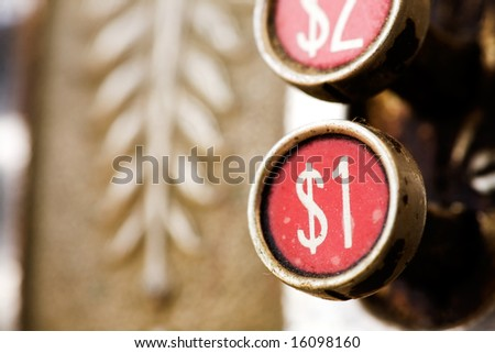 A one dollar button on a retro cash register - shallow depth of field. - stock photo
