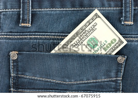 A one hundred dollar note in the back pocket of denim trousers - stock photo
