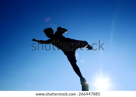 A one man silhouette jumping flying kicking playing, with blue sunny sky on background - stock photo