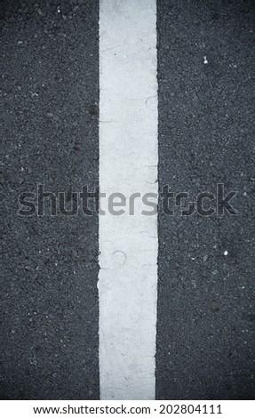 A one way arrow symbol on a black asphalt road surface. - stock photo