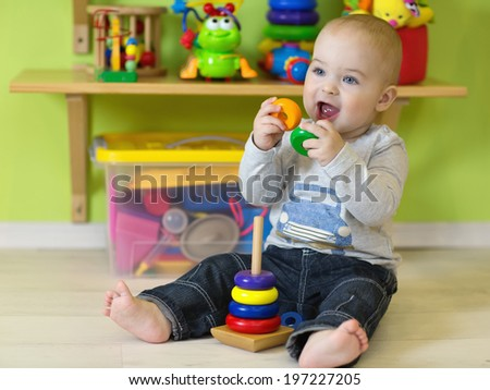 A one year old child playing in his room - stock photo