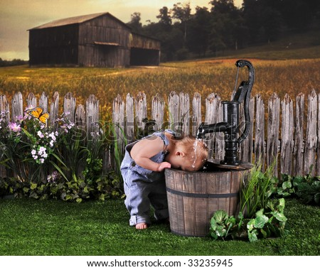 A one-year-old dunking his head under the running spigot of a old water pump in a rural setting. - stock photo