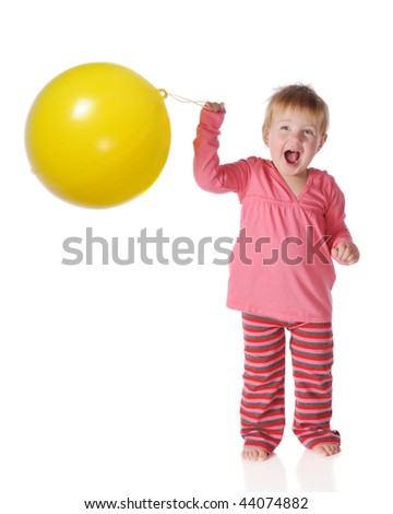 A one-year-old girl delightedly playing with a big, yellow punch ball.  Isolated on white. - stock photo
