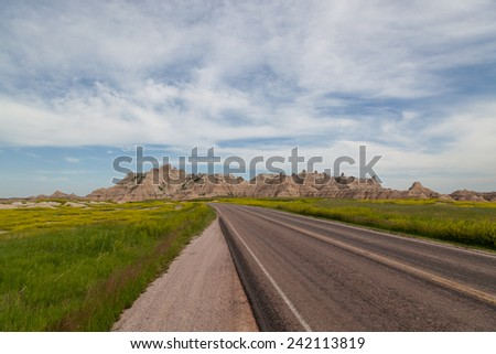 A open country road leads into the awesome mountain formations in Badlands National Park, South Dakota. - stock photo