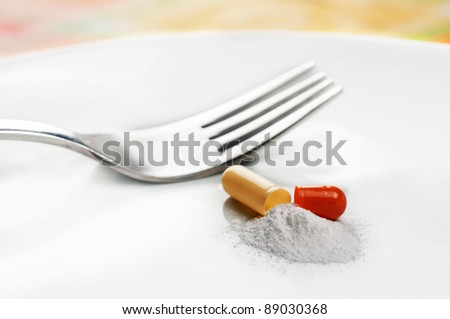 A opened pill on a plate representing a diet pill. - stock photo