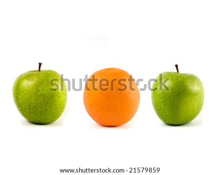 A orange between two green apples on a white background for comparison.