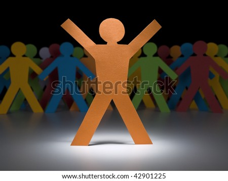 A orange paper figure stands under the spotlight in front of multicolor crew. - stock photo
