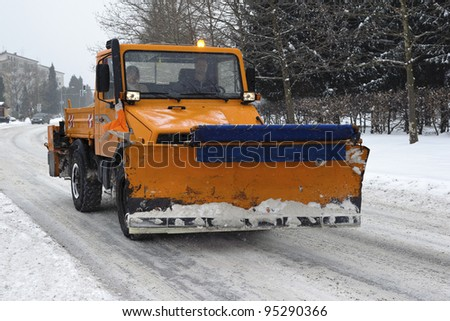 A orange snow plow truck ready for the storm - stock photo
