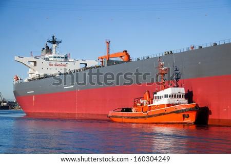A orange tugboat assisting a large oil tanker. - stock photo