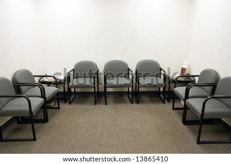 a ordinary waiting room with gray chairs - stock photo