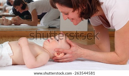 A Osteopathy with baby with blockade on cervical vertebrae - stock photo