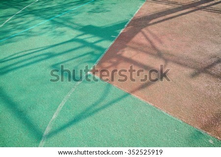 A outdoor basketball court on a playground at school, shadows on it.