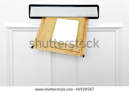 A padded envelope in the letterbox of a white front door, blank label for you to add your own name and address. - stock photo