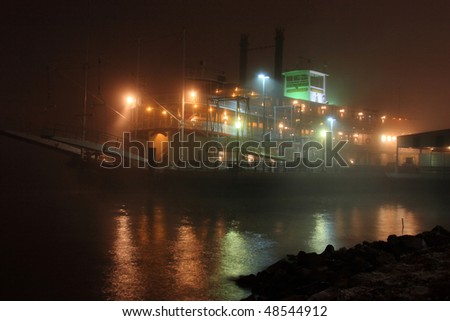 A paddle boat moored on very foggy banks of the Mississippi River in New Orleans, Louisiana - stock photo