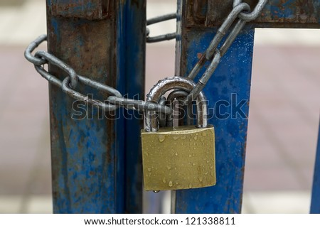 A padlock on an iron blue door