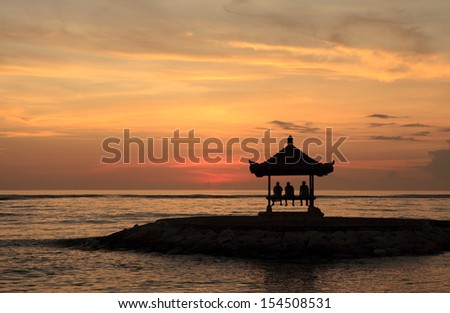 A pagoda on Sanur Beach, Bali, at dawn. There are threee people waiting to see the sun rise. - stock photo