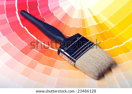 A paint brush over a wheel of colorful paint swatches.