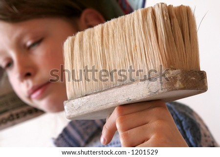 A paintbrush against a background of a young girl