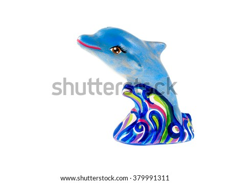 A painted clay figurine of a dolphin jumping out of the sea waves - stock photo