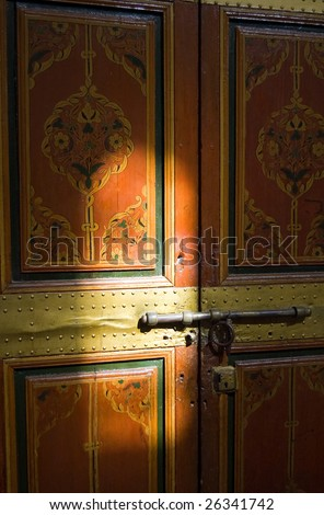 A painted door of the Bahia Palace in Marrakesh with light reflection, Marocco - stock photo