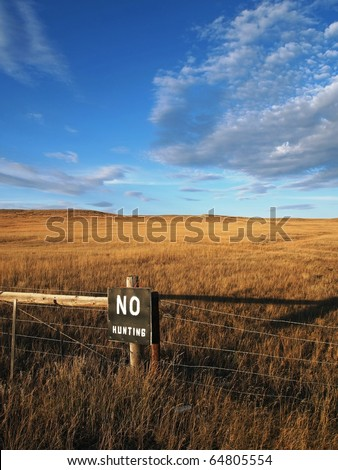 A painted sign warns against hunting the open prairie. - stock photo