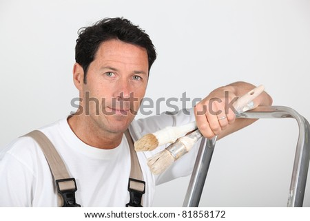 A painter and decorator leaning against a ladder and looking at us. - stock photo