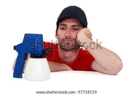 A painter looking a his spray gun. - stock photo