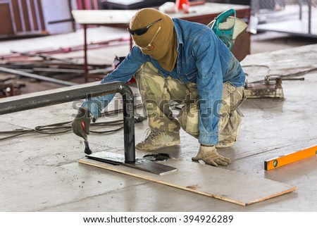 A painter painting black on steel bar. - stock photo