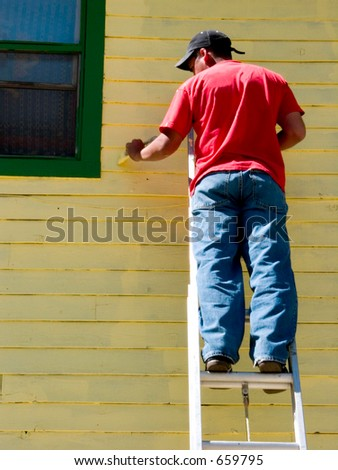 A painter paints an old house a yucky yellow color complemented by green trim. - stock photo