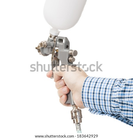 A painter's arm hand holding industrial size spray gun used for industrial painting and coating and isolated on white background - 1 to 1 ratio - stock photo