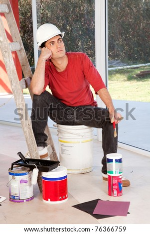 A painter sitting on a paint can, tired and resting - stock photo