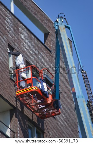 A painter standing recklessly on a aerial access working basket and wearing protective clothing is cleaning a window frame