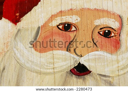 A painting of Santa on plywood.  It is aged and weathered with cracks and peeling paint. - stock photo