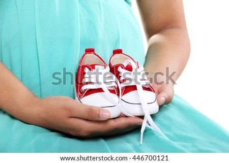 A pair baby shoes on the hands of pregnant mother, close up shot, isolated over white background - stock photo