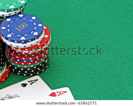 A pair of aces next to a stack of poker chips on a green felt background with copy space - stock photo