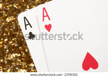A pair of aces with a glittering gold background.